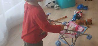 Le petit garçon et la poussette de poupée